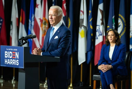 President Joe Biden stands at a podium giving a speech while Vice President Kamala Harris sits on stage. The new administration takes office after four years of Trump Administration policies that wreaked havoc on the lives of refugees and asylum seekers.