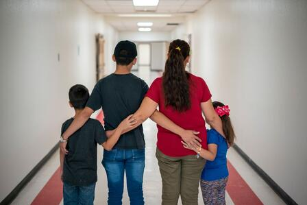 Father, mother, son, and daughter stand arm in arm, backs to the viewer, in a brightly lit hallway