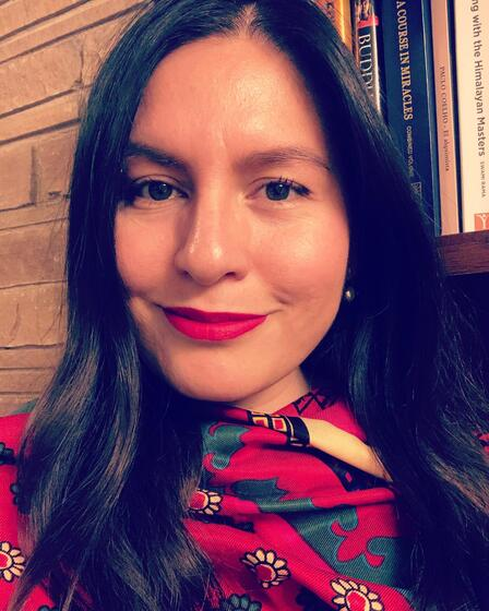 A woman wearing red lipstick smiles, with a bookcase in the background.