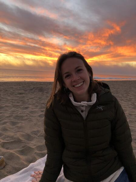 A woman in a coat sitting on a beach, with a colorful sunset in the background.