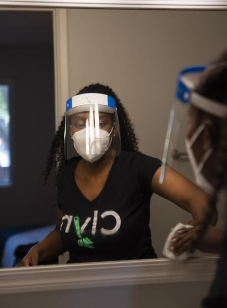 Diana cleans a window while wearing a shirt with the name of her app, Clyn, as well as a face shield and mask.