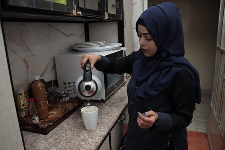 Dr. Bushra pours coffee into a mug.