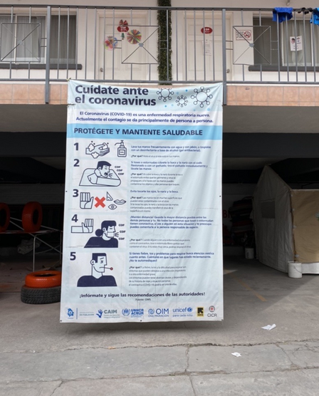 "A banner in Spanish promoting COVID-19 prevention, hanging off of a second floor railing in an old motel that serves as an IRC-supported ""triage hotel"" in Mexico"