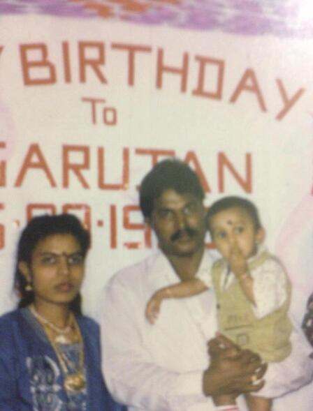 Shanthi and her  husband Sivakumar, who is holding toddler Sarujen, stand in front of a sign that says Happy Birthday to Sarujen