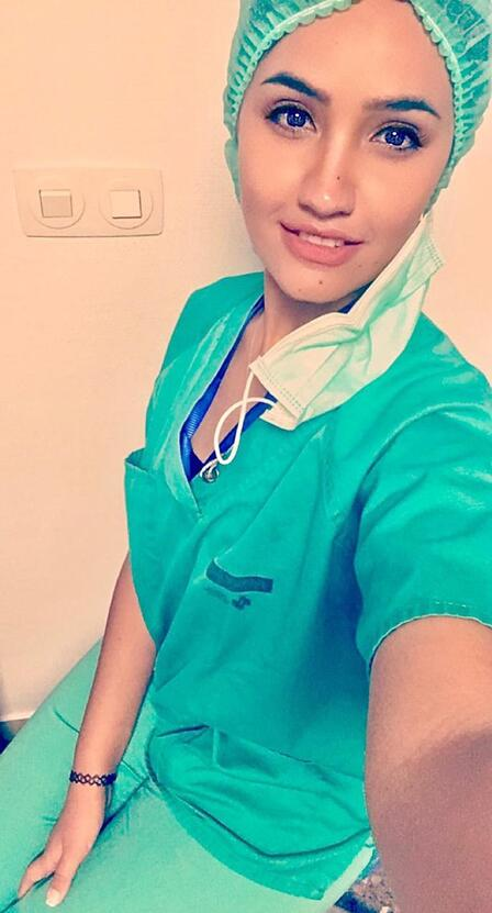 Dr. Rose M. Al-Nsour, wearing blue scrubs, smiles and takes a selfie photo