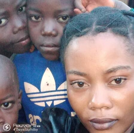 A close up selfie of Mauwa with three of her children, all looking at the camera