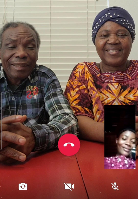 A screenshot of a smart phone, with Patrice and his wife sitting at a table and their daughter Mauwa in a small box on the lower right side of the screen