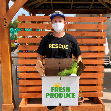 Isaac, an IRC staff member, holds a Fresh Produce Box.
