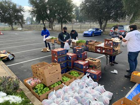 4 members of the Muslim Community Center East Bay organize boxes of food in a parking lot for weekly deliveries to over 200 families
