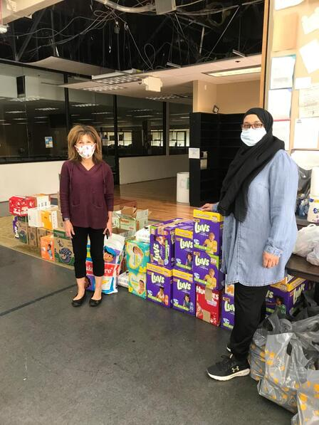 2 MCC volunteers stand next to stacked boxes of diapers to donate to families in need