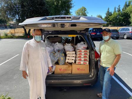 2 MCC members stand next to the back of a car with the hatch open to reveal food donations about to be delivered to families