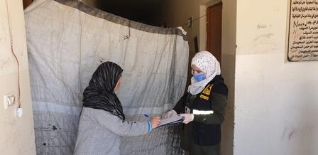 An IRC worker in a face mask to protect against COVID-19 give emergency cash to a Syrian refugee woman in Bekaa, Lebanon.
