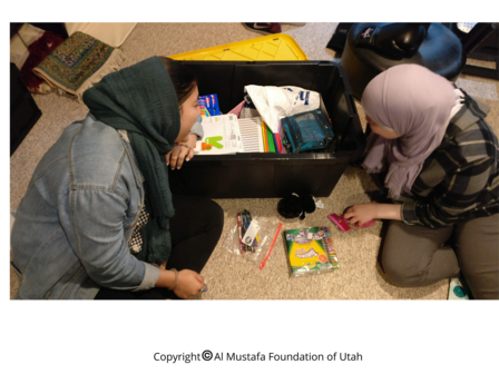 Two children are looking at the gifts they received for Eid al Fitr thorugh the Al-Mustafa Foundation