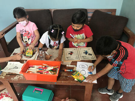 Children sit on a couch drawing pictures and playing games at a coffee table