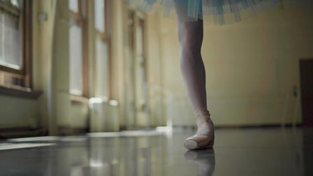 A close-up of the ballerina's leg and point shoe while dancing