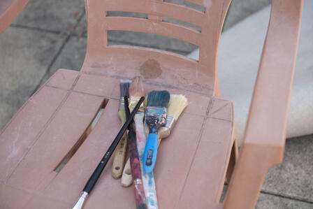 Diala Brisly's paintbrushes sit on a chair on her terrace