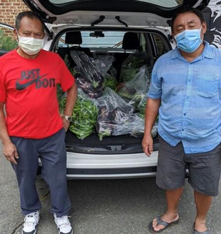 Two men stand in front of a vehicle packed with fresh produce