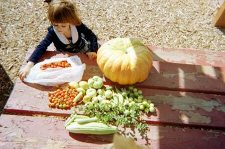 A child sits outside at a table with fresh vegetables