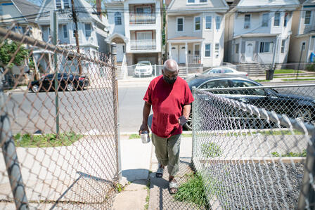 Congolese artist Muyambo Marcel Chishimba walks around a fence and down a paved path into his backyard in Elizabeth, New Jersey