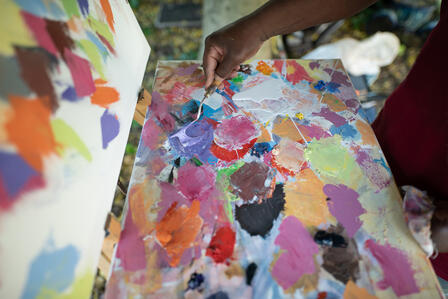 A closeup of artist Muyambo Marcel Chishimba's palette, showing many colors of oil paint