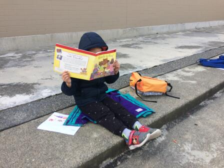 An elementary school student in a blue jacket sits on concrete steps, reading a book which covers their face. Their backpack and homework sit beside them on the concrete steps.