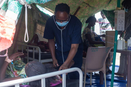 A health worker wearing PPE examines a woman stretched out on a cot at an IRC health center in Sudan.