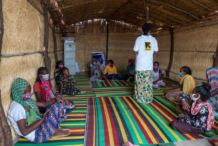 An IRC staff member wearing an IRC logo t-shirt speaks with children and adults sitting on mats on the floor in an IRC safe space for Tigrayan refugees in Sudan.