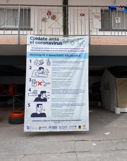 """Una pancarta en español que promueve la prevención del COVID-19, colgada de una barandilla en el segundo piso de un antiguo motel que funciona como un """"hotel de triaje"""" respaldado por el IRC en México."""