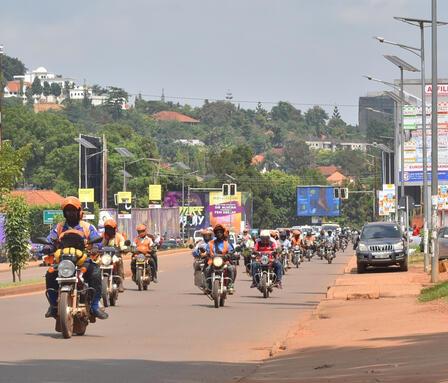 Boda Bodas—motorbike taxis—ride on a wide Kampala street, some carrying passengers.