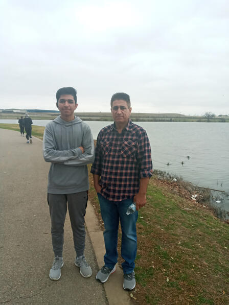 Ehsanullah and his son stand in front of a body of water