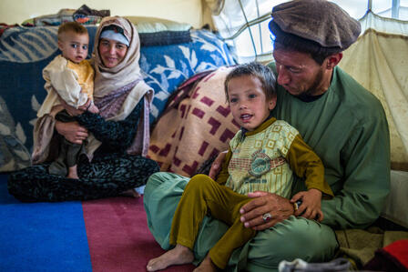 A father and mother from a farming family who were displaced by drought hold their small childen in their laps as they sit on the floor of their tent in Badghis, Afghanistan..
