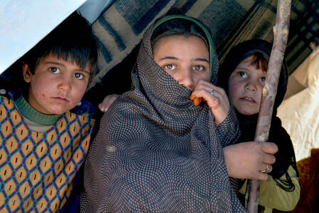 An adolescent girl and two young children look out anixiously from a tent in a camp for displaced Afghan families.