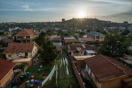 A photo of a landscape during a sunny afternoon in Kampala, Uganda. There are houses and green hills.