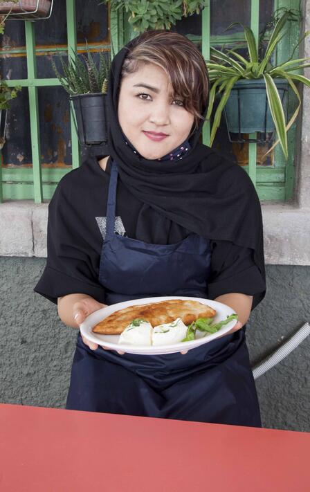 Wearing an apron, Hafeza stands in front of a building holding a plate of Afghan Bolani.