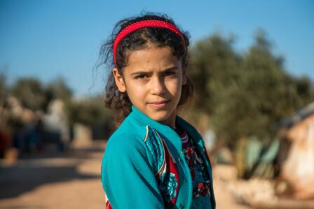 Heba, a ten-year-old Syrian girl stands with a serious expression in the dusty street of the displacement camp where her family lives.