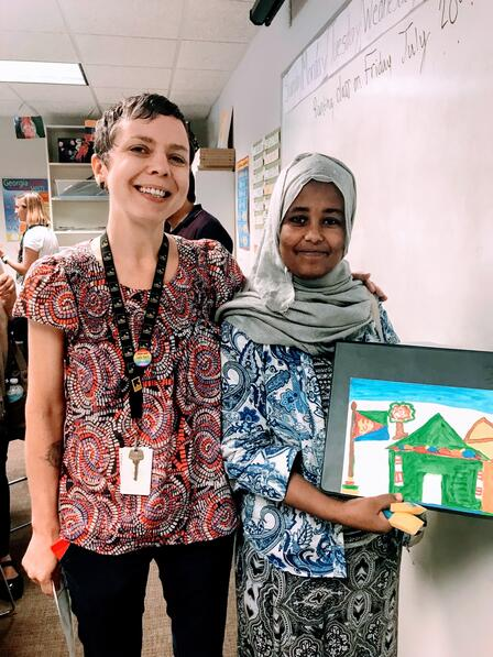 Wende stands with a young woman holding a painting of a house who is a refugee client. They are next to a whiteboard in an Atlanta classroom.