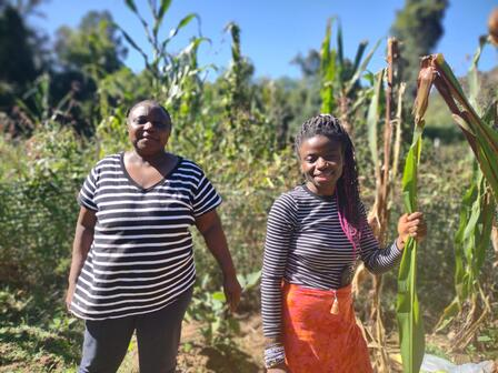 Two women stand in front of corn stalks at a New Roots garden in Charlottesville