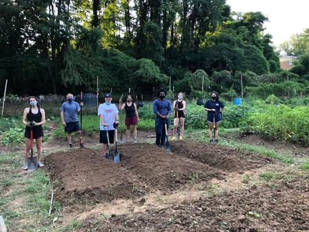 Men and women stand outside, holding garden tools, spaced out in front of three freshly dug garden beds