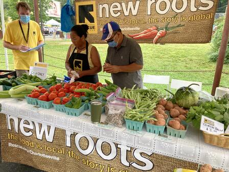 Two men and a women stand behind a table under a tent at a farmers' market display. The table is stacked with produce for sale.