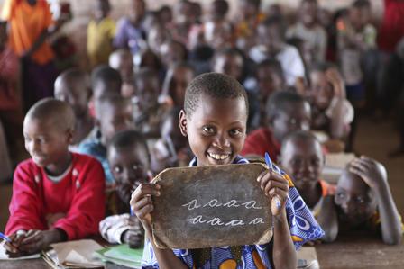 Children in Burundi practice their English letters at school.