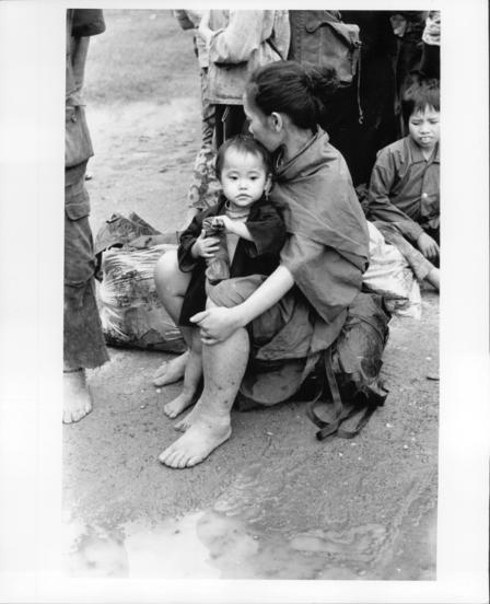 A refugee woman and child from Laos sit on the ground outside, awaiting medical treatment.