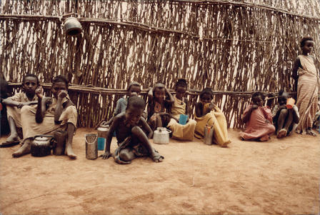 A group of young Ethiopian refugee children sit in the dirt outside a structure made of sticks and branches.