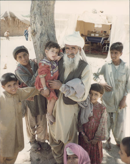 An older man and a number of young boys, all Afghan refugees, pose for a photo outside, in front of a tree.