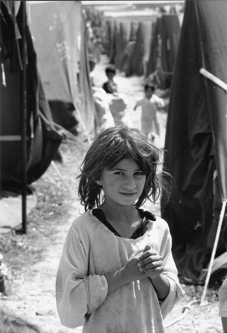 A young Iraqi refugee stands in alone, outside, in a crowded refugee camp in Turkey.