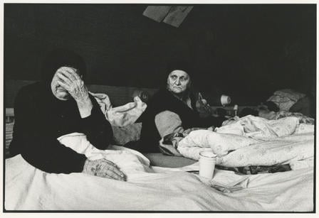 Two Bosnian women lie in beds in a refugee camp in Croatia, one of whom is crying.