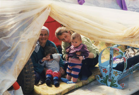 Two Kosovar refugee women, and two infant children, sit inside a tent.