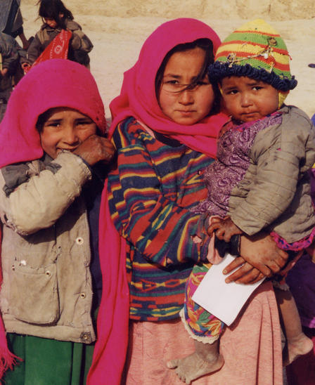 Three young Afghan girls in bright pink clothing pose for a picture.