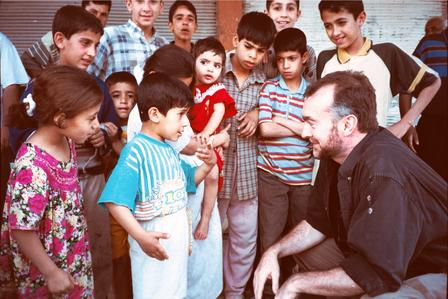 A middle aged man squats down as he talks with a group of Iraqi children.