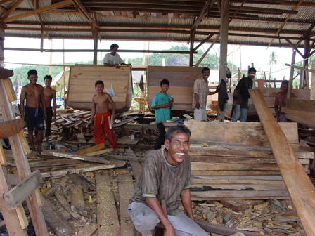 A group of Indonesians work together in a large wooden building, attaching pieces of wood together to build boats.
