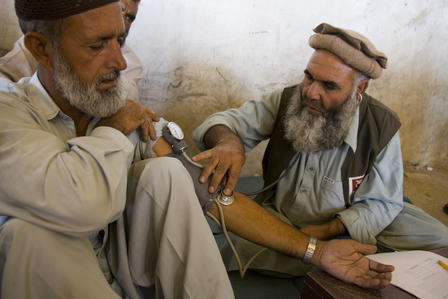 A doctor and another man, both Pakistani, sit on the floor, as the doctor takes the blood pressure of the other man.